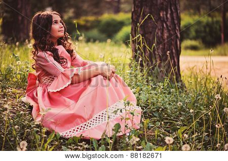 happy curly girl in pink fairytale princess dress in the forest