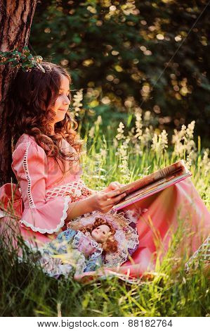 happy curly girl in pink fairytale princess dress reading book in the forest