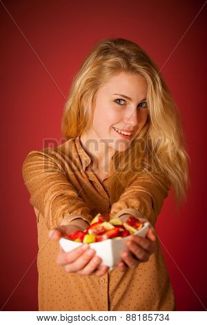 Beautiful Young Caucasian Blonde Woman Holds A Delicious Fruit Salad As A Sign For Healthy Eating Ov