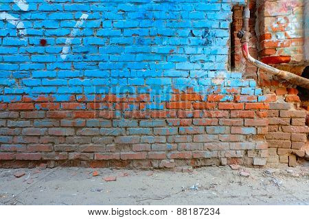 Old brick wall half painted in bright blue color and rusty water pipe, a lot of copyspace