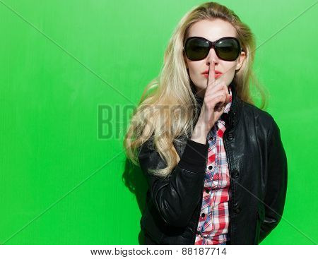 Beautiful blond girl  summer sunny day in the black jacket and lips finger asking for silence