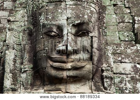 The stone face of the khmer king on the wall of Bayon Temple
