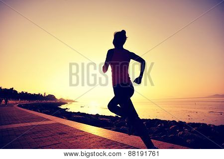 young woman runner running at seaside. woman fitness silhouette sunrise jogging workout wellness con