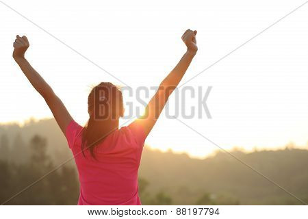 cheering young asian woman open arms at sunrise mountain peak