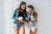 image of denim jeans  - Two beautiful girls friends reading the magazine wearing sunglasses and denim jeans jackets and shorts urban street casual style - JPG