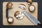 picture of champignons  - Several brown sliced champignon mushrooms on a wooden chopping board with knife - JPG
