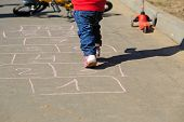 picture of hopscotch  - little girl playing hopscotch on asphalt outside - JPG