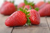 foto of foreground  - two strawberries closeup on the foreground and on blurred background heap of strawberries - JPG