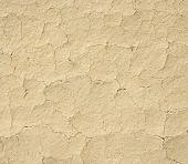 stock photo of shaky  - Cracked mud plaster wall closeup in sun - JPG