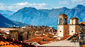 stock photo of red roof tile  - Top view with tiled red roofs and mountains in Kotor old city in Montenegro - JPG