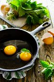 picture of nettle  - Scrambled eggs with nettles in a pan on a wooden table - JPG