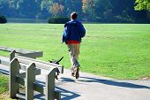 stock photo of dog park  - teen boy jogging with black dog