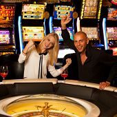 picture of roulette table  - Young Couple Playing Roulette In Casino Betting And Winning - JPG