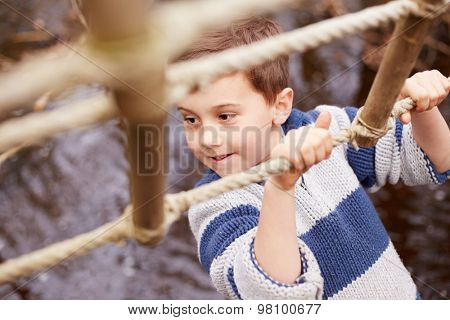 Boy Crossing Stream On Rope Bridge At Activity Centre
