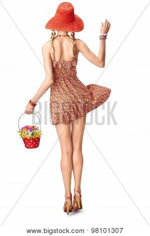 Joyful boho woman in sundress with basket of wildflowers