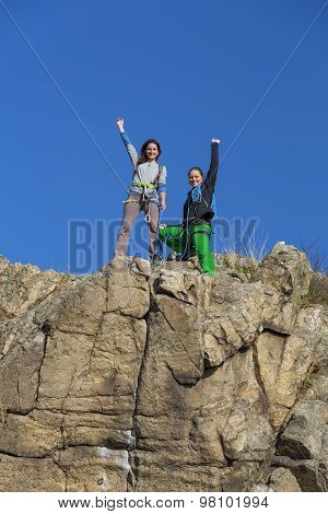 Group of two happy female climbers that are just conquered the summit stays over the rocky wall