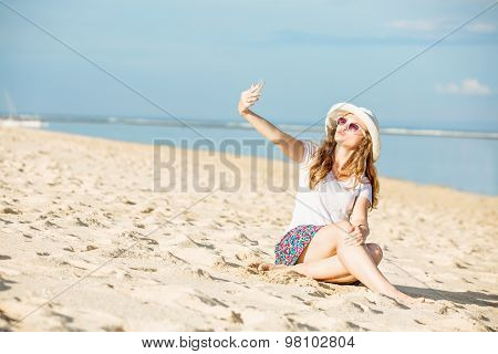 Beautiful young woman on the beach at sunny day taking selfie with phone