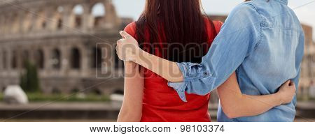 people, homosexuality, same-sex marriage, travel and gay love concept - close up of happy lesbian couple hugging over coliseum in rome background