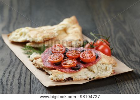 sandwich with pita bread salami and vegetables on table