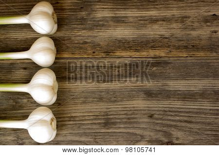 Fresh Garlic Bulbs With Long Stalk On Wood Table With Copy Space