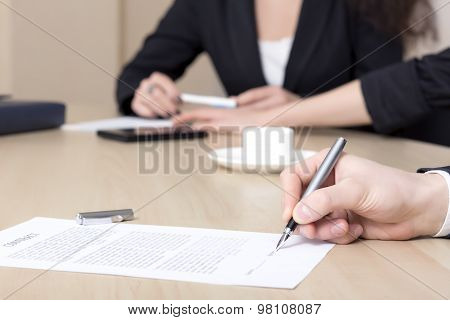 Female businessperson signs contract