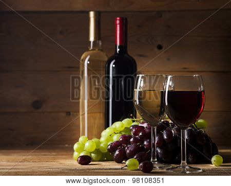 Red and white wine on wooden background