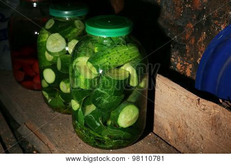 Home preserved cucumbers in glass jars in cellar, closeup