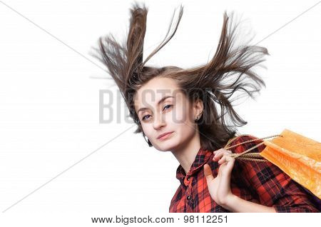 Young Woman With Long Blowing Hair And Shoping Bags
