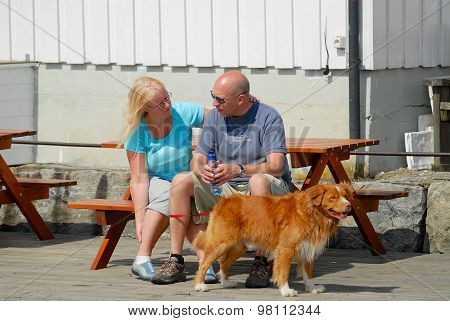 People with a dog rest at the bench in Frogn, Norway.