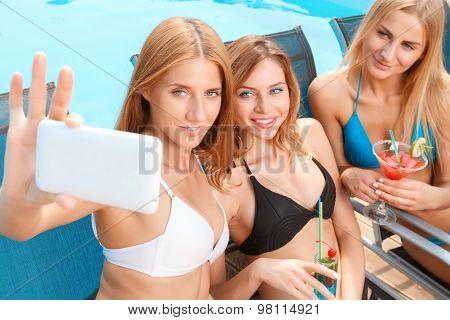 Girlfriends doing selfie at pool