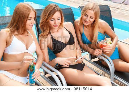 Girlfriends on chaise longue near pool