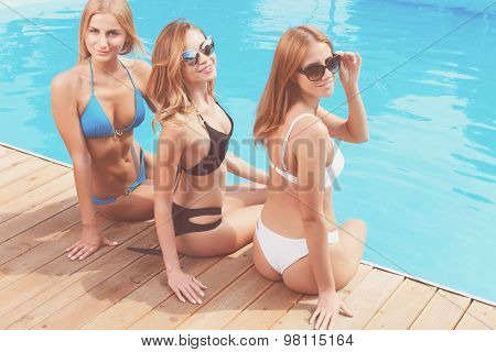 Three girlfriends chilling at poolside