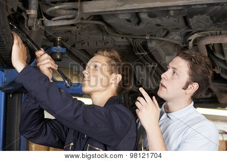 Mechanic And Apprentice Working On Car Together