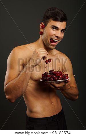 Man eats red fresh cherry