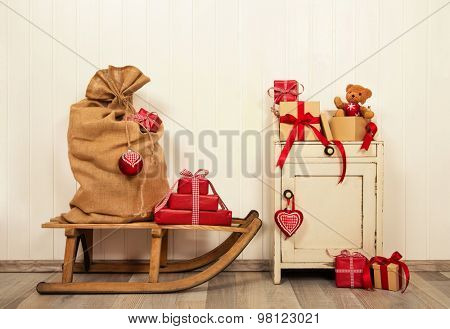 Christmas presents in red and white in vintage style on old wooden background with sledge.