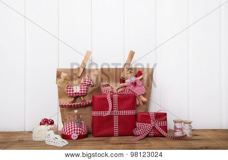 Handmade christmas presents wrapped in red paper with checked ribbon on wooden white background for decoration.