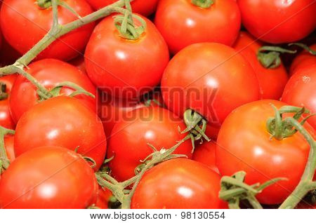Red Background -  Close Up Of Fresh Tomatoes Offered For Sale In A Marketplace