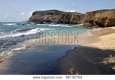 White, Black Sand Beach By The Cliff