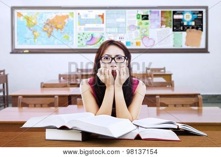 Confused Brunette Student With Book In Class