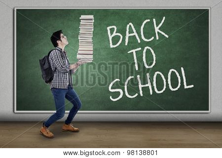 Student Back To School And Carrying A Pile Of Book