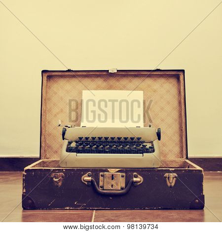 an old typewriter with a blank page in its roller, placed in an old suitcase, with a retro effect