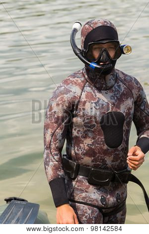 The guy in a diving suit. Diving, diving in the river.