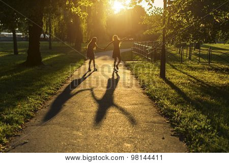 Silhouettes of two girls walking down the alley holding hands, during amazing sunset.