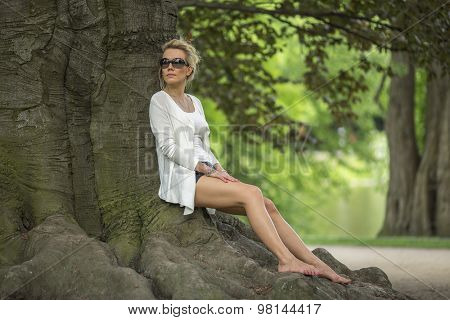 Young beautiful woman sitting on the roots of a tree in the Park.
