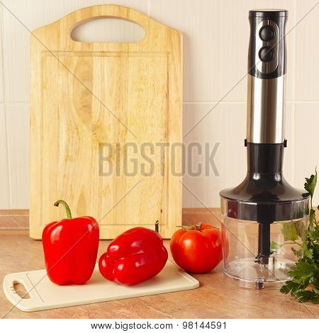 Red bellpepper with tomato and a blender on kitchen table