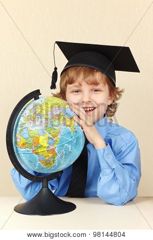 Little smiling professor in academic hat with globe