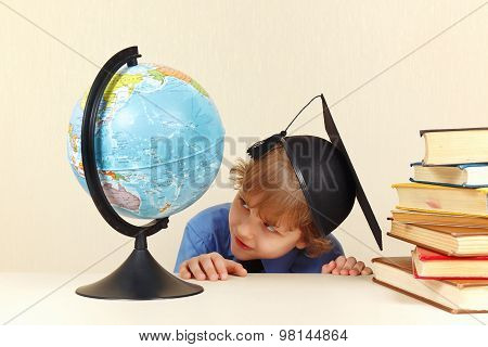 Little professor in academic hat looks at geographical globe