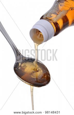 Honey dripping from a spoon isolated on white