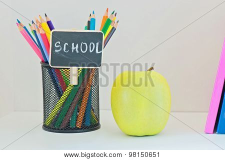Yellow apple, pencils in case and multi colored books