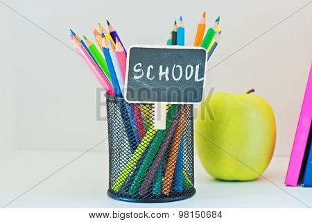 Pencils in holder, yellow appleand book